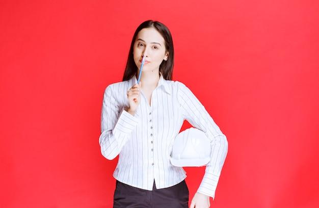 Foto di una bella donna d'affari che tiene il cappello di sicurezza sul muro rosso.