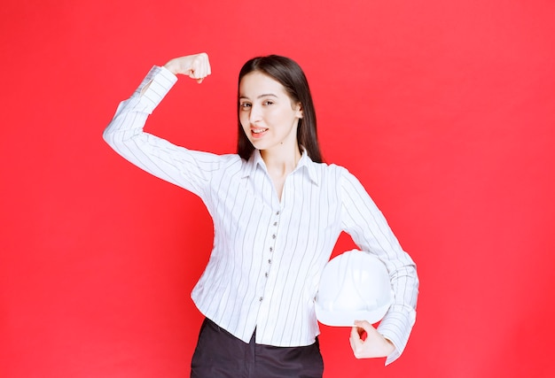 Photo of a beautiful business woman holding safety hat and showing muscle .
