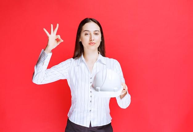 Foto di una bella donna d'affari che tiene il cappello di sicurezza e mostra il gesto giusto.