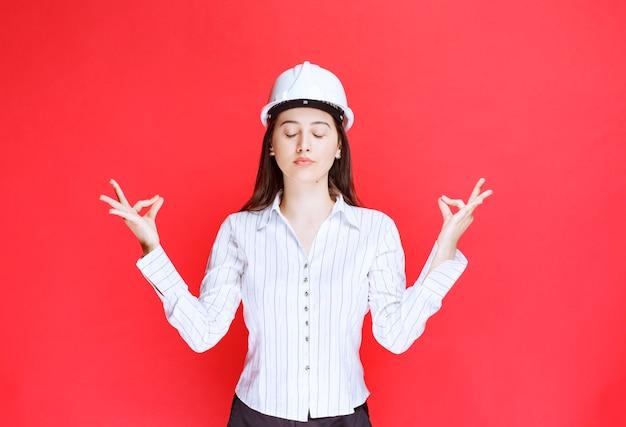 Foto di una bella donna d'affari che indossa un cappello di sicurezza meditando contro il muro rosso.
