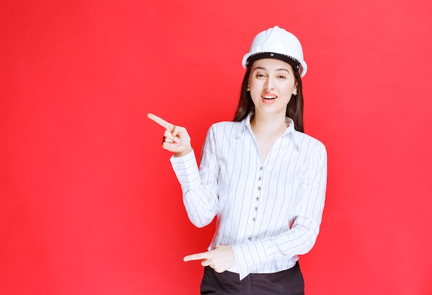 Photo of a beautiful business woman wearing safety hat pointing away with fingers.