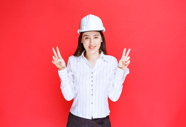 Photo of a beautiful business woman wearing safety hat showing victory sign .