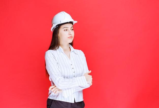 Foto di una bella donna d'affari che indossa un cappello di sicurezza in piedi con le braccia incrociate.