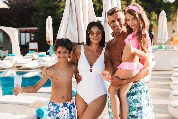 Photo of beautiful caucasian family with children resting near luxury swimming pool with white fashion deckchairs and umbrellas outdoor, during recreation or tourism