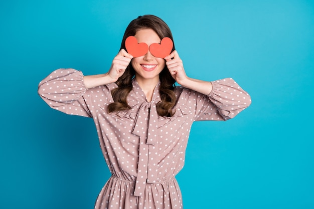 Photo of beautiful charming funny lady wavy hairdo hold two little red heart cards hiding eyes shy person romantic mood wear dotted dress isolated blue color background