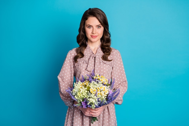 Photo of beautiful cute charming lady wavy hairdo hold large big wildflowers surprise bunch present secret admirer delivery service wear dotted dress isolated blue color background