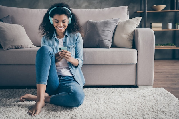 Photo of beautiful dark skin wavy lady homey mood holding telephone wear cool earflaps listening new audio sitting floor near couch casual denim outfit living room indoors