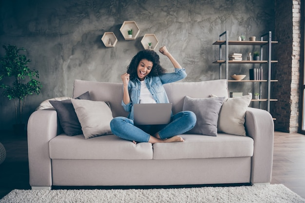 Photo of beautiful dark skin wavy lady notebook on knees crossed legs celebrating first investment to freelance project sitting cozy couch casual denim outfit living room indoors