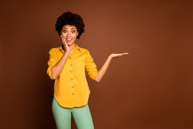 Photo of beautiful excited dark skin curly lady holding open palm novelty product discount price hand on cheek wear yellow shirt green trousers isolated brown color