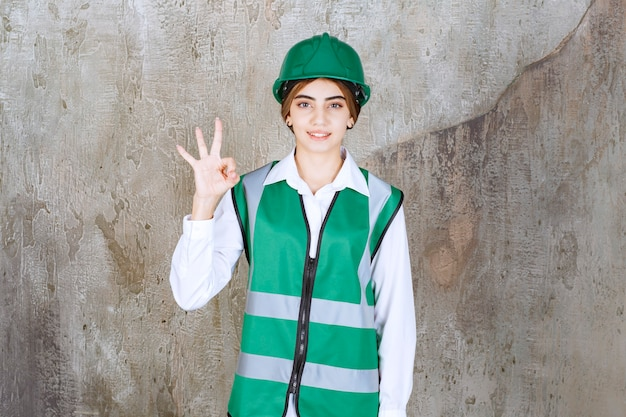 Photo of beautiful female architect in green helmet giving ok sign