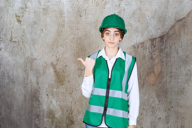 Photo of beautiful female architect in green helmet pointing