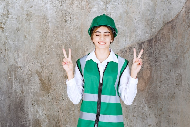 Photo of beautiful female architect in green helmet showing victory sign