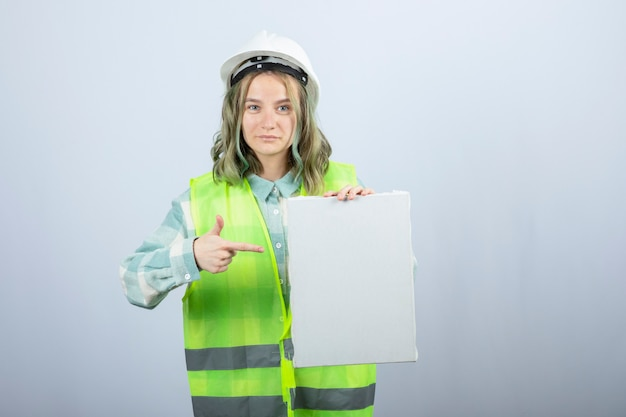 Photo of beautiful female engineer holding empty canvas over white wall. high quality photo