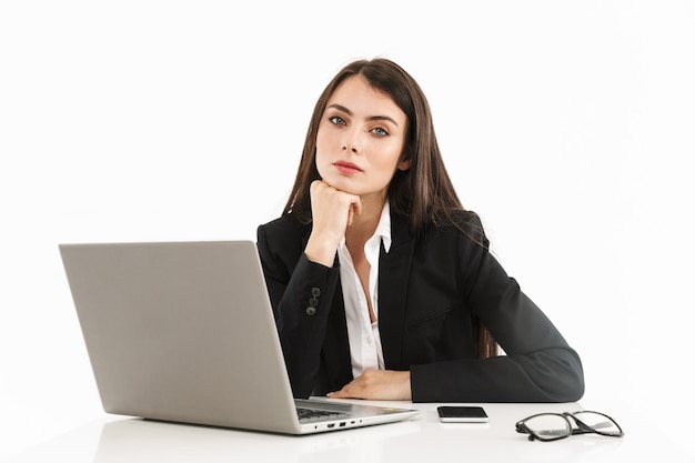 Photo of beautiful female worker businesswoman dressed in formal wear sitting at desk and working on laptop in office isolated over white wall