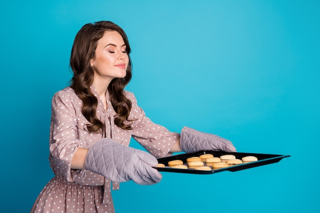 Photo of beautiful funny lady hold big fresh home bakery tray gloves wait guests prepared little cookies heart shape enjoy tasty smell wear dotted dress isolated blue color background