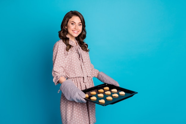 Photo of beautiful funny lady wavy hairdo hold big fresh home bakery tray gloves wait guests prepared little cookies heart shape wear dotted dress isolated blue color background