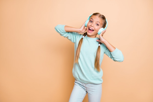 Photo of beautiful funny little lady enjoy listen cool wireless earphones favorite song good mood open mouth wear blue pullover jeans isolated beige pastel color wall