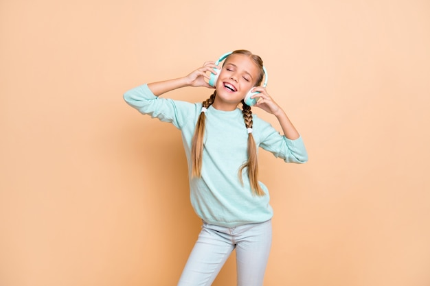 Photo of beautiful funny little lady eyes closed enjoy listen cool wireless earphones favorite song wear blue pullover jeans isolated beige pastel color wall