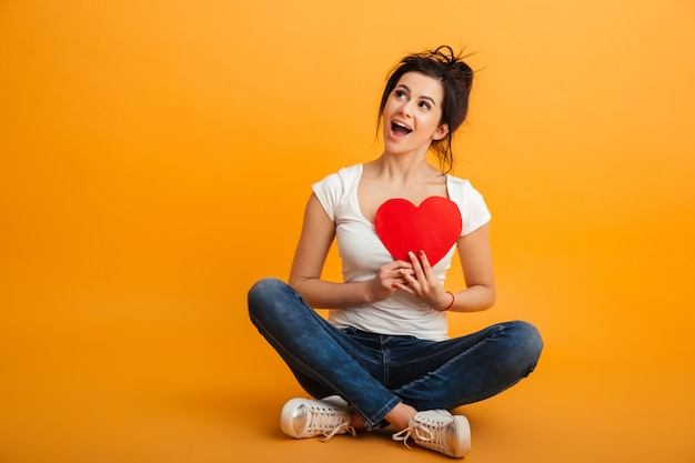 Photo of beautiful girl 20s wearing eyeglasses and sneakers sitting with legs crossed on the floor and holding paper red heart in hands, over yellow wall