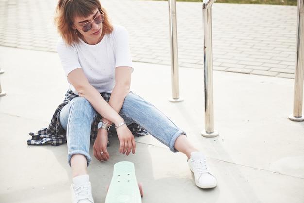 Una foto di una bella ragazza con bei capelli tiene uno skateboard su una lunga tavola e sorridente, vita urbana.
