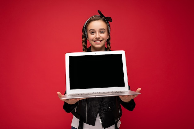Photo of beautiful happy smiling girl with brunet pigtails holding computer laptop wearing black