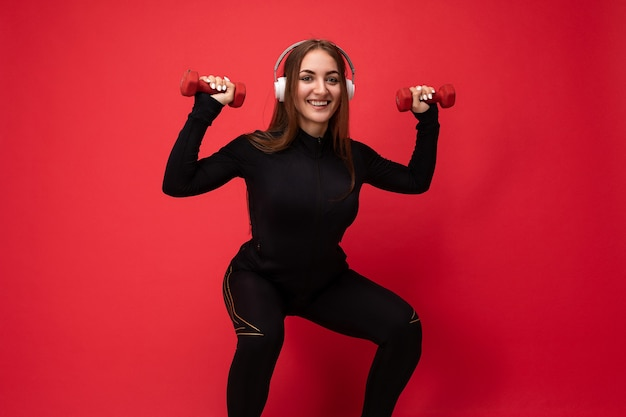 Photo of beautiful happy smiling young brunet woman wearing black sport clothes isolated on red background wall squating wearing white bluetooth headsets listening to music looking at camera.