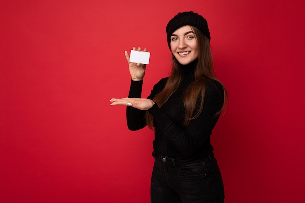 Photo of beautiful happy young brunette woman wearing black sweater and hat isolated on red wall holding and showing credit card .