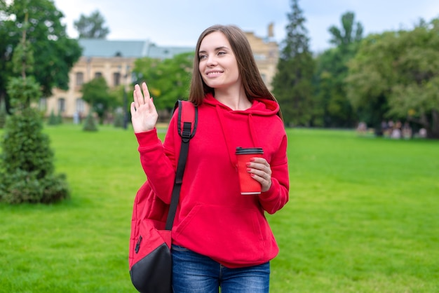 Photo of beautiful lady enjoying nice takeaway takeout beverage latte tea going to lessons waving palm to somebody