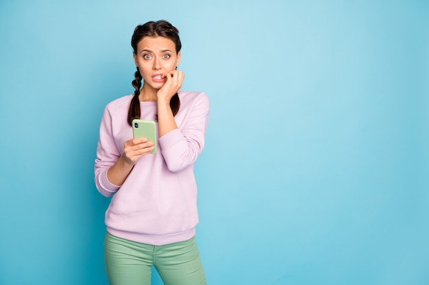 Photo of beautiful lady hold telephone crowd know secret private information biting fingers scared celebrity wear casual pink sweater green pants isolated blue color