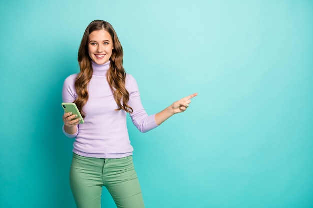Photo of beautiful lady hold telephone indicating finger side empty space advising cool low prices wear purple turtleneck pastel green pants isolated teal color