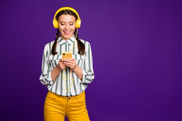 Photo of beautiful lady holding telephone positive mood vacation time listen music wear cool earflaps striped shirt yellow trousers isolated purple color background