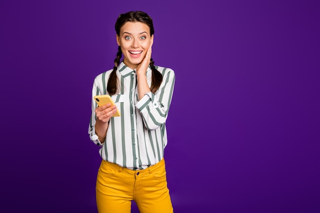 Photo of beautiful lady holding telephone reading instagram post positive good comments and likes wear striped shirt yellow trousers isolated purple color background