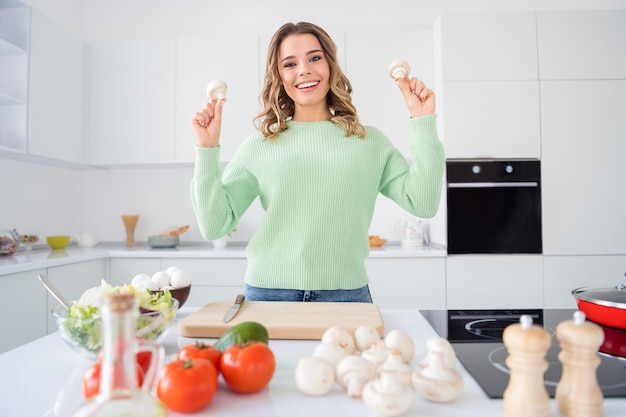 Photo of beautiful lady holding two fresh mushrooms