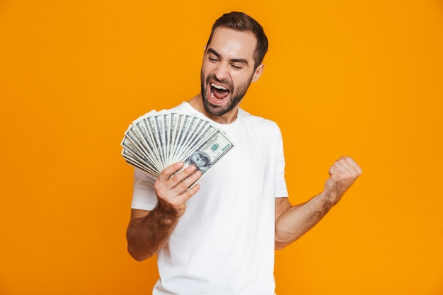 Photo of beautiful man 30s in casual wear holding bunch of money, isolated
