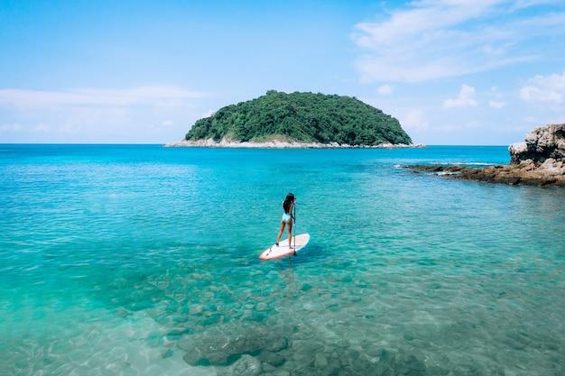 Photo of a beautiful posing woman standing on a kayak