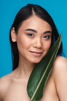 Photo of a beautiful positive smiling asian young woman posing isolated on blue wall with green plant leaf.