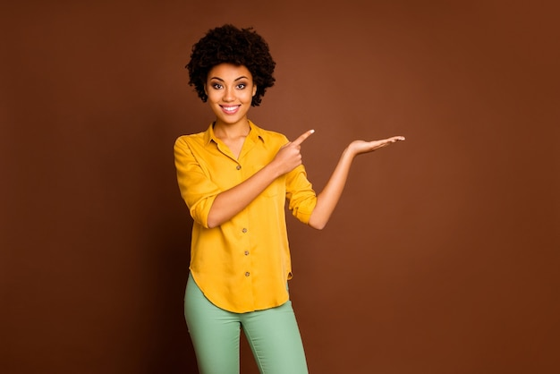 Photo of beautiful pretty dark skin wavy lady holding open palm novelty product discount price indicate finger offer buy wear yellow shirt green pants isolated brown color