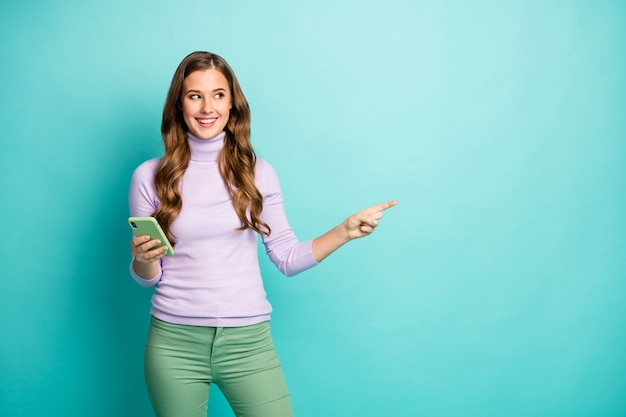Photo of beautiful pretty lady hold telephone indicating finger look empty space advising low device prices wear purple turtleneck green pants isolated teal pastel color