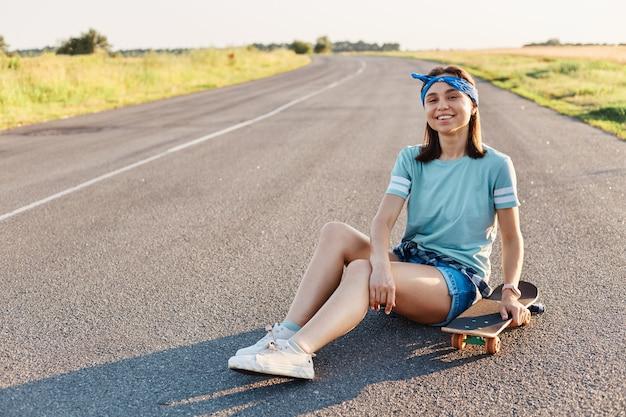 Foto di una bella donna sorridente che indossa maglietta, fascia per capelli e corta, seduta per strada con longboard, guardando la telecamera con un sorriso a trentadue denti, esprimendo felicità, godendosi il tempo libero.