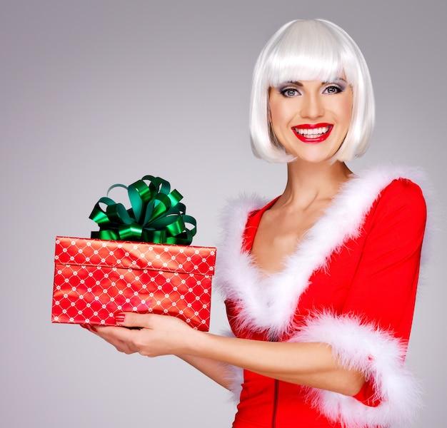 La foto della bella fanciulla delle nevi tiene la confezione regalo di natale e capodanno