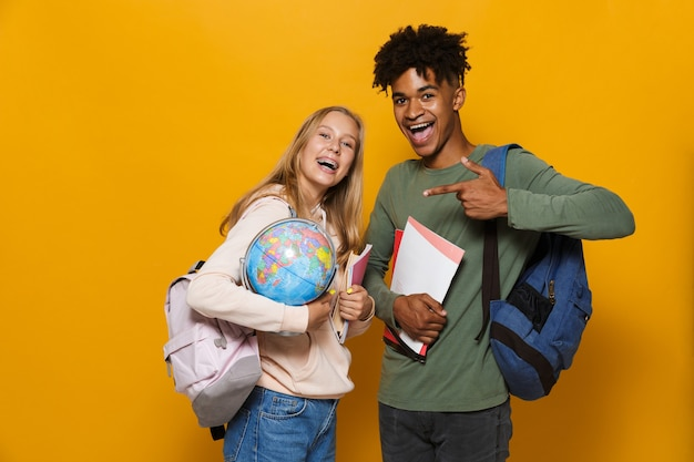 Photo of beautiful students man and woman 16-18 wearing backpacks holding earth globe and exercise books, isolated over yellow background