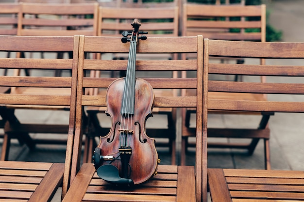 Photo of beautiful violin in open air on wooden chair.