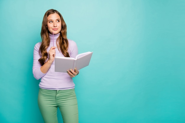 Photo of beautiful wavy lady hold planner write creative business idea in journal looking up empty space deep thinking wear lilac sweater green pants isolated teal pastel color