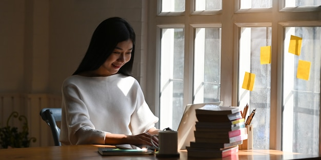 Photo of beautiful woman holding a smartphone in her hands while sitting at the wooden table in front computer laptop, coffee cup, stack of books and notebook in orderly library.