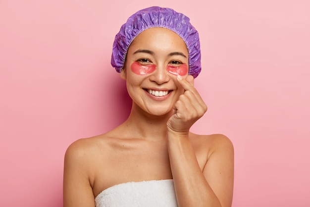 Photo of beautiful woman makes korean hand sign, expresses love, shows finger heart gesture, wears bath cap, stands wrapped in towel, applies cosmetic eyes patches, smiles happily .