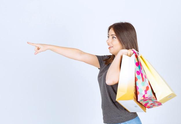 Foto di una bellissima modella che porta le borse della spesa e che punta con il dito indice.