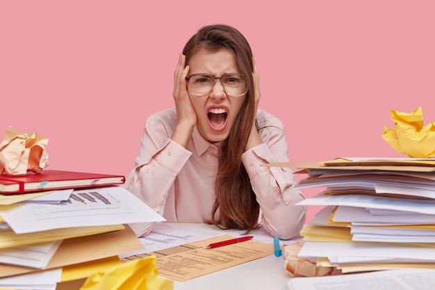 Foto di bella donna in preda al panico, grida di depressione e frustrazione, ha molto lavoro e scadenza
