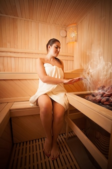 Photo of beautiful woman sitting next to oven at sauna