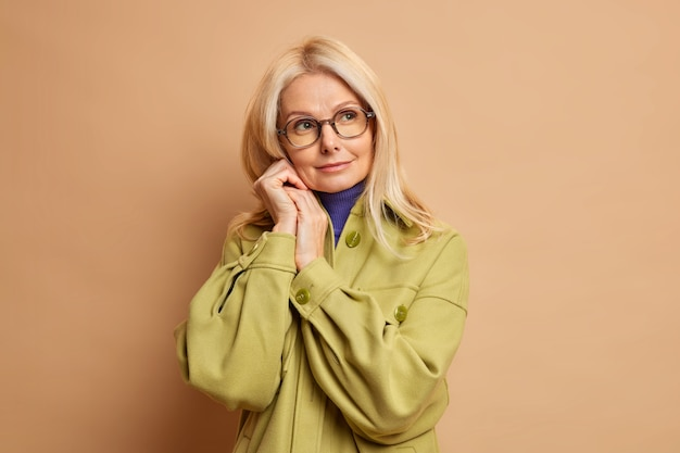Photo of beautiful wrinkled fifity years old woman keeps hands near face and looks aside pensively dressed in fashionable coat.