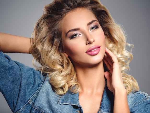 Foto di una bellissima giovane ragazza bionda con i capelli ricci. primo piano attraente sensuale viso di donna bianca con i capelli lunghi. trucco occhi smokey.